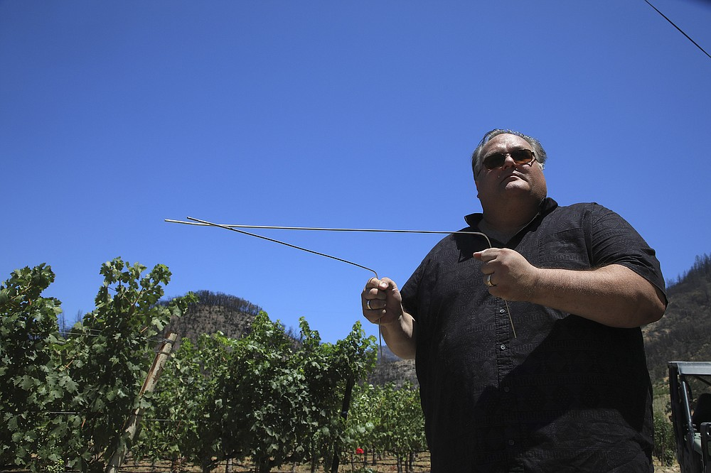 """**EMBARGO: No electronic distribution, Web posting or street sales before 3:01 a.m. ET Saturday, July 17, 2021. No exceptions for any reasons. EMBARGO set by source.** Rob Thompson with the stainless steel """"L"""" rods he uses while dowsing for water at a Napa Valley vineyard in Calistoga, Calif., July 13, 2021. Amid California's drought, desperate landowners and managers are turning to those who practice an ancient, disputed method for locating water. (Jim Wilson/The New York Times)"""