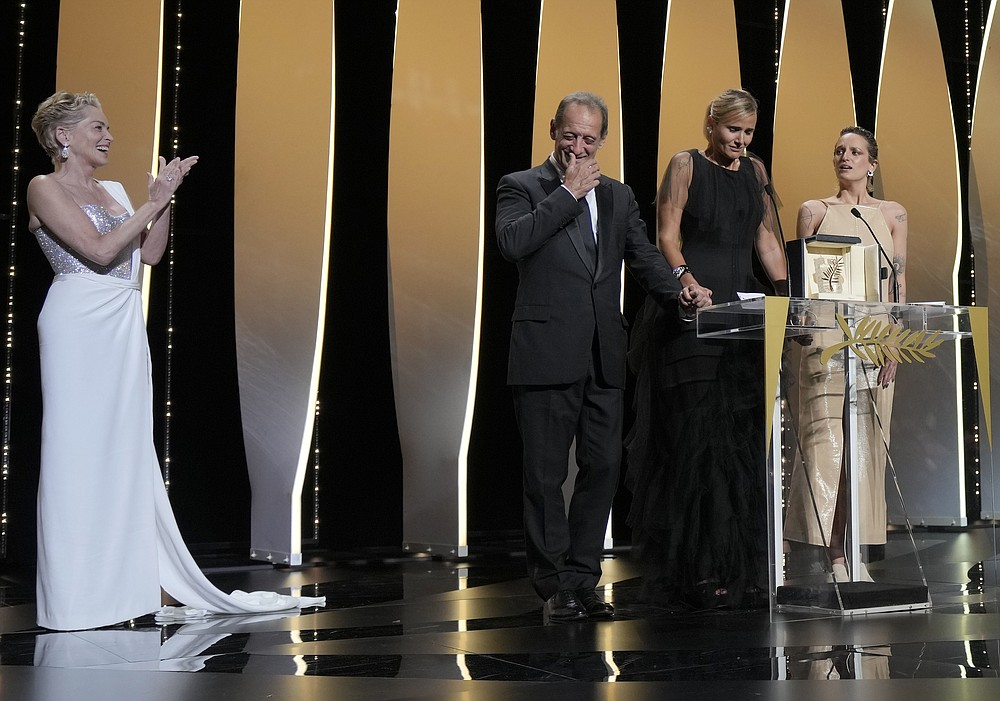 Sharon Stone, left, looks on as Vincent Lindon, from second left, director Julia Ducournau, and Agathe Rousselle accept the Palme d'Or for the film 'Titane' during the awards ceremony for the 74th international film festival, Cannes, southern France, Saturday, July 17, 2021. (AP Photo/Vadim Ghirda)