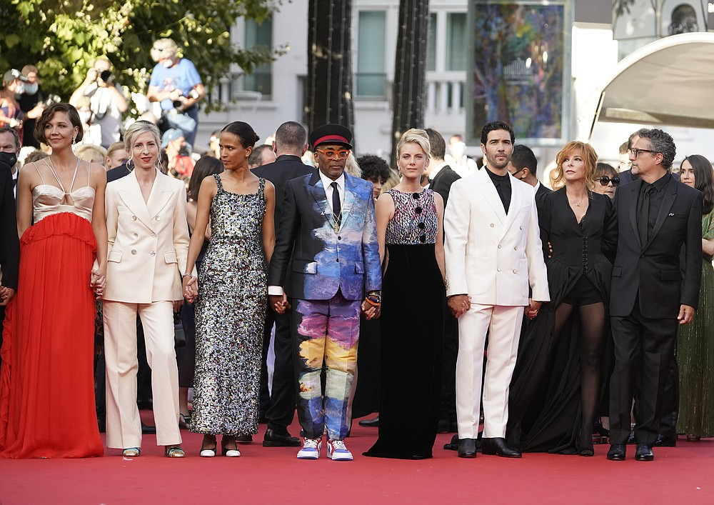 Jury members Maggie Gyllenhaal, from left, Jessica Hausner, Mati Diop, Spike Lee, Melanie Laurent,Tahar Rahim, Mylene Farmer, and Kleber Mendonca Filho poses for photographers upon arrival at the awards ceremony and premiere of the closing film 'OSS 117: From Africa with Love' at the 74th international film festival, Cannes, southern France, Saturday, July 17, 2021. (AP Photo/Brynn Anderson)
