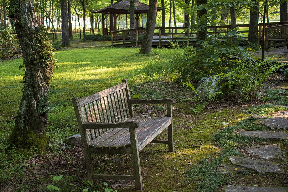 A bench offers rest to visitors in the Asian Woodland Garden at Wildwood Park for the Arts. (Arkansas Democrat-Gazette/Cary Jenkins)