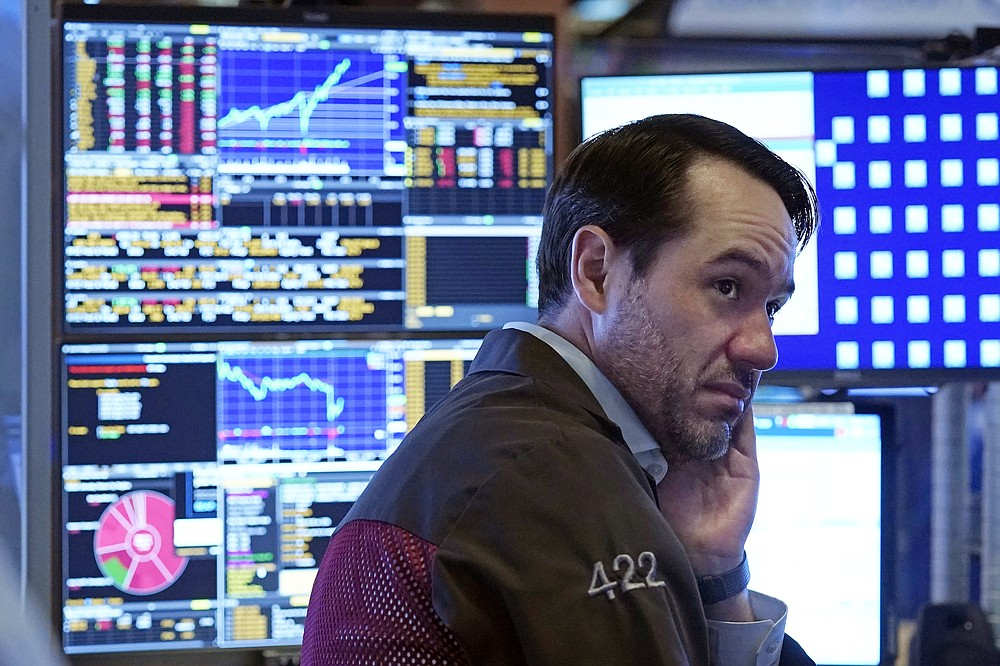 A trader works in a booth on the floor of the New York Stock Exchange, Monday, July 19, 2021. Stocks are falling sharply Monday as worries sweep from Wall Street to Sydney that the worsening pandemic in hotspots around the world will derail what's been a strong economic recovery. (AP Photo/Richard Drew)