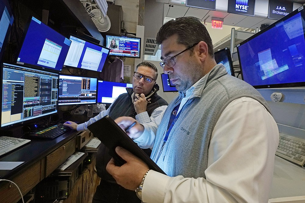Traders Jonathan Mueller, left, and Michael Capolino work on the floor of the New York Stock Exchange, Monday, July 19, 2021. Stocks are falling sharply Monday as worries sweep from Wall Street to Sydney that the worsening pandemic in hotspots around the world will derail what's been a strong economic recovery. (AP Photo/Richard Drew)