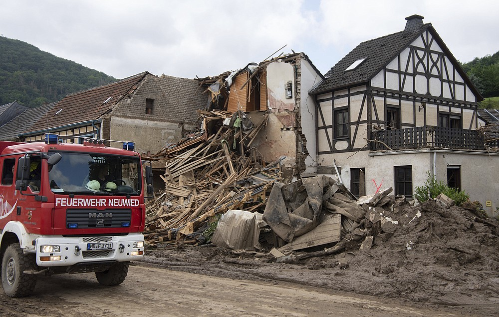 Firefighters stand in front of a destroyed house in Altenahr, Germany, Monday, July 19, 2021. Numerous houses in the town were completely destroyed or severely damaged, there are numerous fatalities. (Boris Roessler/dpa via AP)