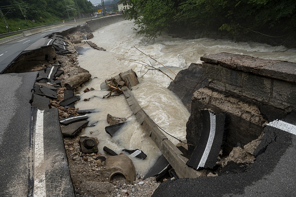 A federal road is swept away by the floodwaters in the Ramsauer Ache near Berchtesgaden, Germany Monday, July 19, 2021.  About 130 people were evacuated in Germany's Berchtesgaden area after the Ache River swelled. (Peter Kneffel/dpa via AP)