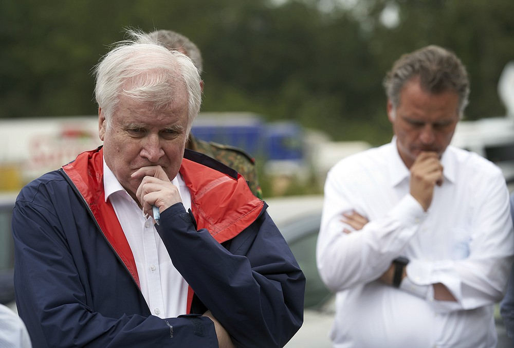 Federal Minister of the Interior Horst Seehofer, left, gives a press statement during a visit to the Federal Agency for Technical Relief (THW), which is on flood duty there in Bad Neuenahr, Germany, Monday, July 19, 2021.  (Thomas Frey/dpa via AP)
