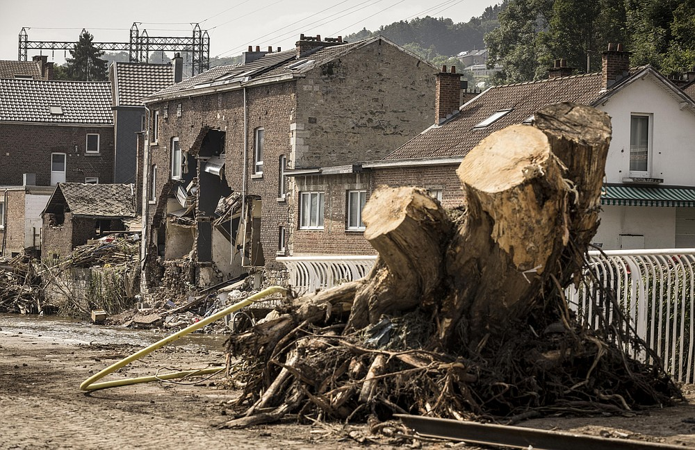 A large tree stump stands in the street among damaged houses in Pepinster, Belgium, Monday, July 19, 2021. Residents in several provinces continued to clean up after severe flooding in Germany and Belgium turned streams and streets into raging torrents that swept away cars and caused houses to collapse. (AP Photo/Valentin Bianchi)