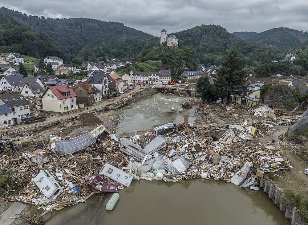 Caravans, gas tanks, trees and scrap pile up metres high on a bridge over the Ahr in Altenahr, Germany, Monday, July 19, 2021. Numerous houses in the town were completely destroyed or severely damaged, there are numerous fatalities. (Boris Roessler/dpa via AP)