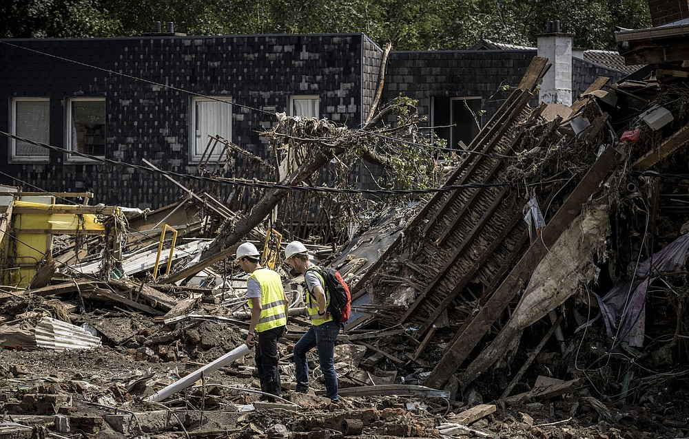 Workers look through the rubble of houses after flooding in Liege, Belgium, Monday, July 19, 2021. Residents in several provinces continued to clean up after severe flooding in Germany and Belgium turned streams and streets into raging torrents that swept away cars and caused houses to collapse. (AP Photo/Valentin Bianchi)