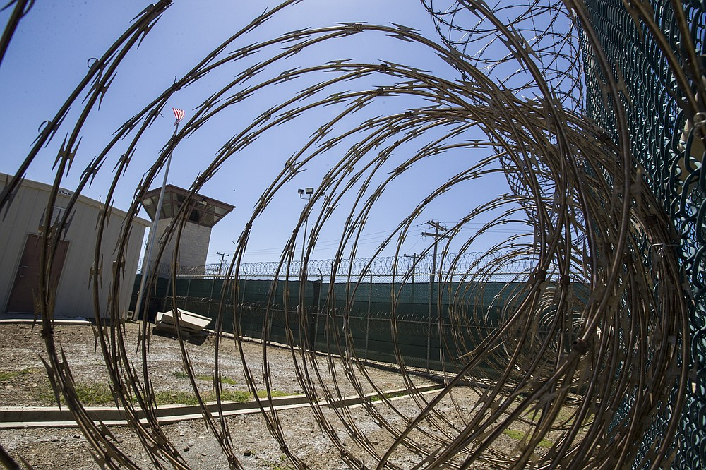 FILE - In this Wednesday, April 17, 2019 file photo reviewed by U.S. military officials, the control tower is seen through the razor wire inside the Camp VI detention facility in Guantanamo Bay Naval Base, Cuba. The Biden administration has transferred a detainee out of the Guantánamo Bay detention facility for the first time, sending a Moroccan man back home years after he was recommended for discharge. (AP Photo/Alex Brandon, File)