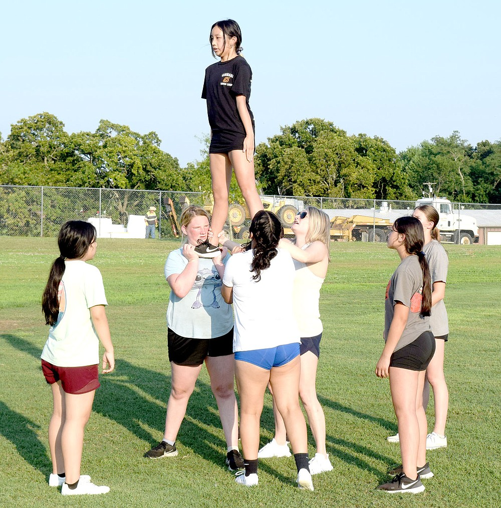 Westside Eagle Observer/MIKE ECKELS McKenzie Thao stands tall as she and the Decatur cheer team perform a prep stunt at Bulldog Stadium in Decatur July 13, The cheerleaders, led by Shara Coffelt, will show off the team's talent during the first home football game in mid-September.