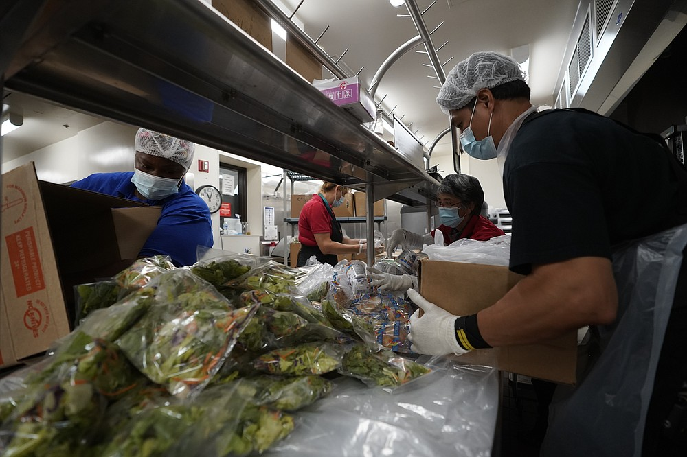 Los Angeles Unified School District food service workers from left, April Thomas, Marisel Dominguez, Tomoko Cho, and Aldrin Agrabantes pre-package hundreds of free school lunches in plastic bags on Thursday, July 15, 2021, at the Liechty Middle School in Los Angeles. Flush with cash from an unexpected budget surplus, California is launching the nation's largest statewide universal free lunch program. When classrooms open for the fall term, every one of California's 6.2 million public school students will have the option to eat school meals for free, regardless of their family's income. (AP Photo/Damian Dovarganes)