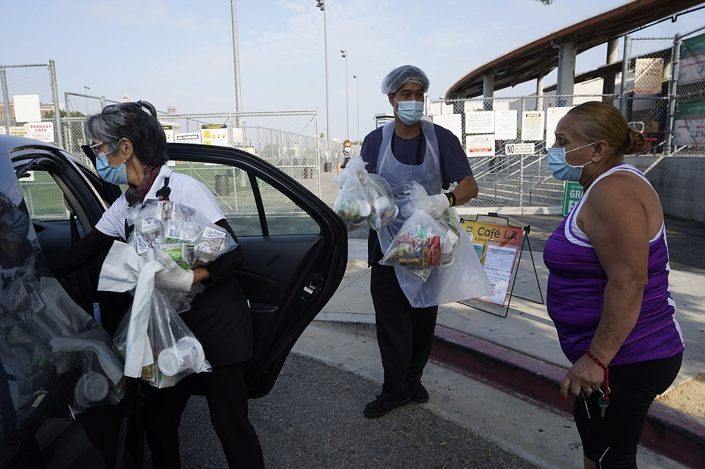 Los Angeles Unified School District food service workers, Tomoko Cho, left, and Aldrin Agrabantes help parent Celia Contreras load her free school lunches in to her vehicle on Friday, July 16, 2021, at the Liechty Middle School in Los Angeles. Flush with cash from an unexpected budget surplus, California is launching the nation's largest statewide universal free lunch program. When classrooms open for the fall term, every one of California's 6.2 million public school students will have the option to eat school meals for free, regardless of their family's income. (AP Photo/Damian Dovarganes)