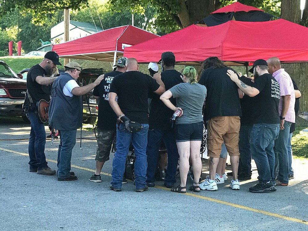 COURTESY PHOTO Photo from previous Unchained Summer Concert showing a group praying together. The goal of the event is to glorify God and share the gospel.