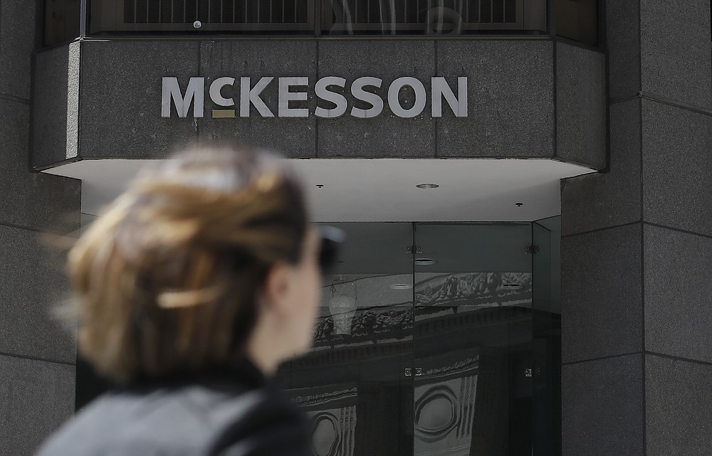 FILE - In this July 17, 2019, file photo, a pedestrian passes a McKesson sign on an office building in San Francisco. A $26 billion settlement between the three biggest U.S. drug distribution companies and drugmaker Johnson & Johnson and thousands of states and municipalities that sued over the toll of the opioid crisis is certainly significant, but it is far from tying a neat bow on the tangle of still unresolved lawsuits surrounding the epidemic. (AP Photo/Jeff Chiu, File)