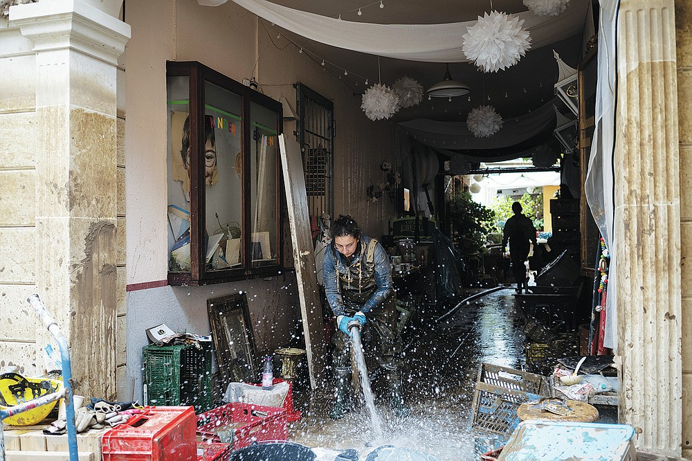 A restaurant owner pumps out water from her basement that was flooded in Bad Neuenahr-Ahrweiler, Germany, Monday July 19, 2021. More than 180 people died when heavy rainfall turned tiny streams into raging torrents across parts of western Germany and Belgium, and officials put the death toll in Ahrweiler county alone at 110. (AP Photo/Bram Janssen)