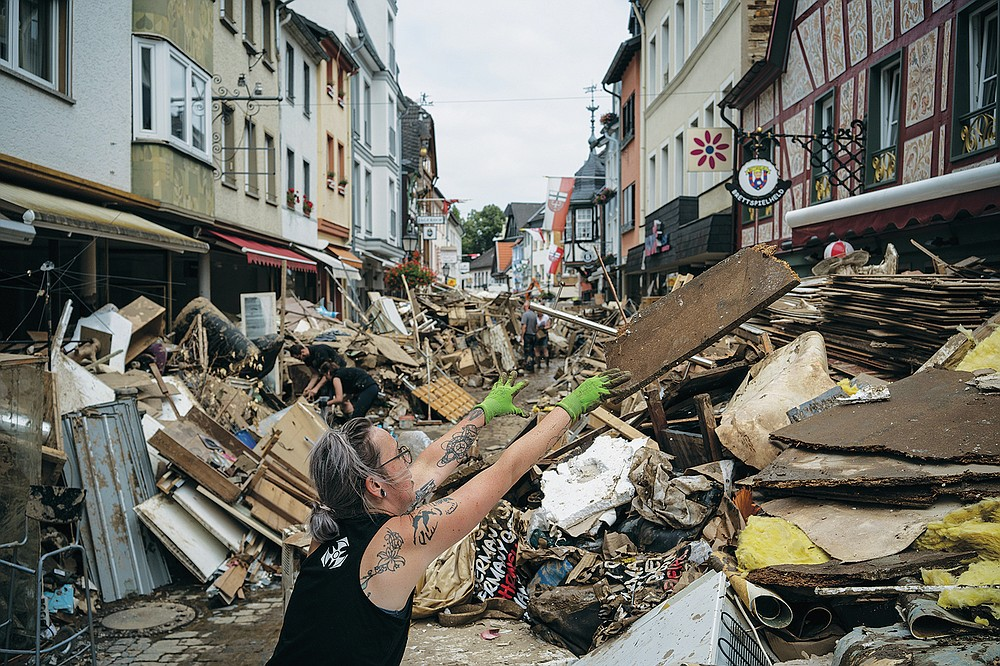 A woman throws away rubbish in the center of Bad Neuenahr-Ahrweiler, Germany, Monday July 19, 2021. More than 180 people died when heavy rainfall turned tiny streams into raging torrents across parts of western Germany and Belgium, and officials put the death toll in Ahrweiler county alone at 110. (AP Photo/Bram Janssen)
