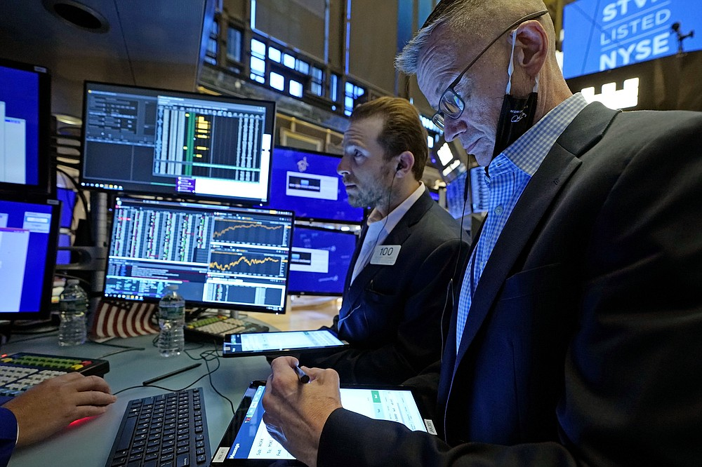 Traders Ben Tuchman, left, and Neil Catania work on the floor of the New York Stock Exchange, Tuesday, July 20, 2021. Stocks are opening higher on Wall Street Tuesday as investors shake off a rout a day earlier brought on by concerns about the spread of a more contagious variant of COVID-19. (AP Photo/Richard Drew)