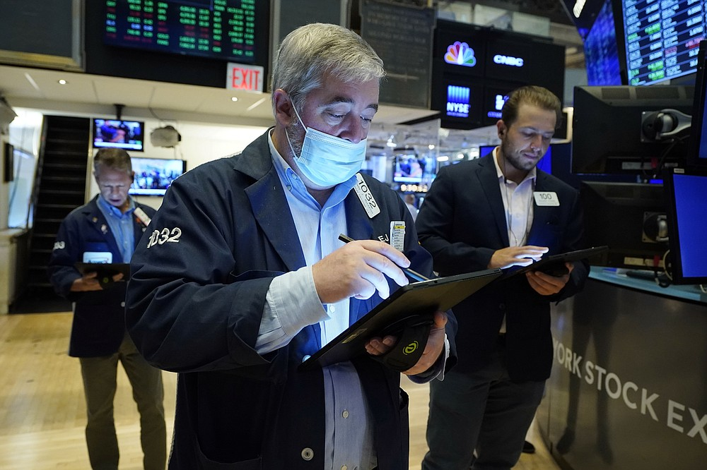 Edward McCarthy, center, works with fellow traders on the floor of the New York Stock Exchange, Tuesday, July 20, 2021. Stocks are opening higher on Wall Street Tuesday as investors shake off a rout a day earlier brought on by concerns about the spread of a more contagious variant of COVID-19. (AP Photo/Richard Drew)