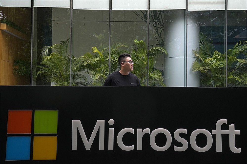 A man stands watch outside the Microsoft office building in Beijing, Tuesday, July 20, 2021. The Biden administration and Western allies formally blamed China on Monday for a massive hack of Microsoft Exchange email server software and asserted that criminal hackers associated with the Chinese government have carried out ransomware and other illicit cyber operations. (AP Photo/Andy Wong)