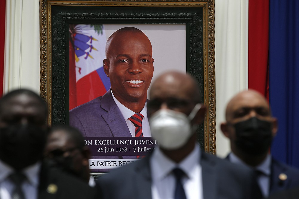 Authorities pose for a group photo in front of the portrait of late Haitian President Jovenel Moise at at the National Pantheon Museum during his memorial service in Port-au-Prince, Haiti, Tuesday, July 20, 2021. Moise was assassinated on July 7 at his home. (AP Photo/Joseph Odelyn)