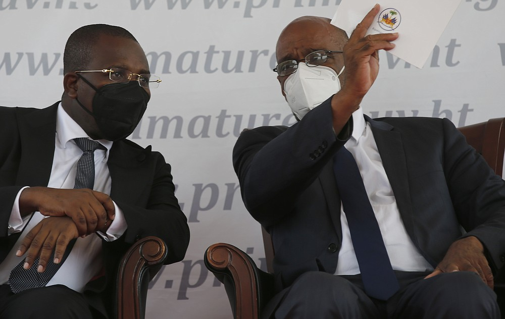 Haiti's designated Prime Minister Ariel Henry, right, and interim Prime Minister Claude Joseph speak during Henry's appointment as the new prime minister in Port-au-Prince, Haiti, Tuesday, July 20, 2021, weeks after the assassination of President Jovenel Moise on July 7. (AP Photo/Joseph Odelyn)