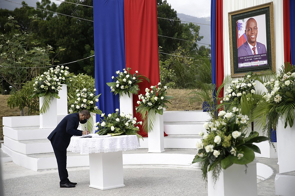 A man puts his name into a signature book during a memorial ceremony for late Haitian President Jovenel Moise at the National Pantheon Museum in Port-au-Prince, Haiti, Tuesday, July 20, 2021. Moise was assassinated on July 7 at his home. (AP Photo/Joseph Odelyn)