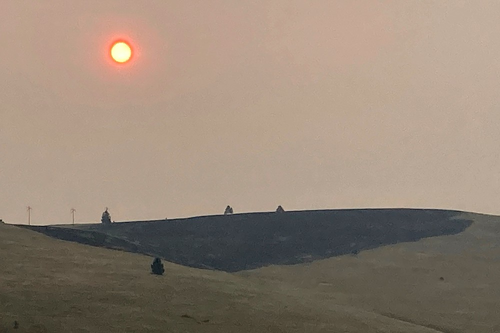 Smoke obscures the air and dims the sun over a hillside burned by a recent wildfire, in Missoula, Mont., on Sunday, July 18, 2021. Extreme heat descended on parts of the U.S. northern Rocky Mountains on Monday, July 19 as authorities struggled to contain dozens of wildfires burning in a region parched by prolonged drought and blanketed with dangerous smoke. (AP Photo/Matthew Brown)
