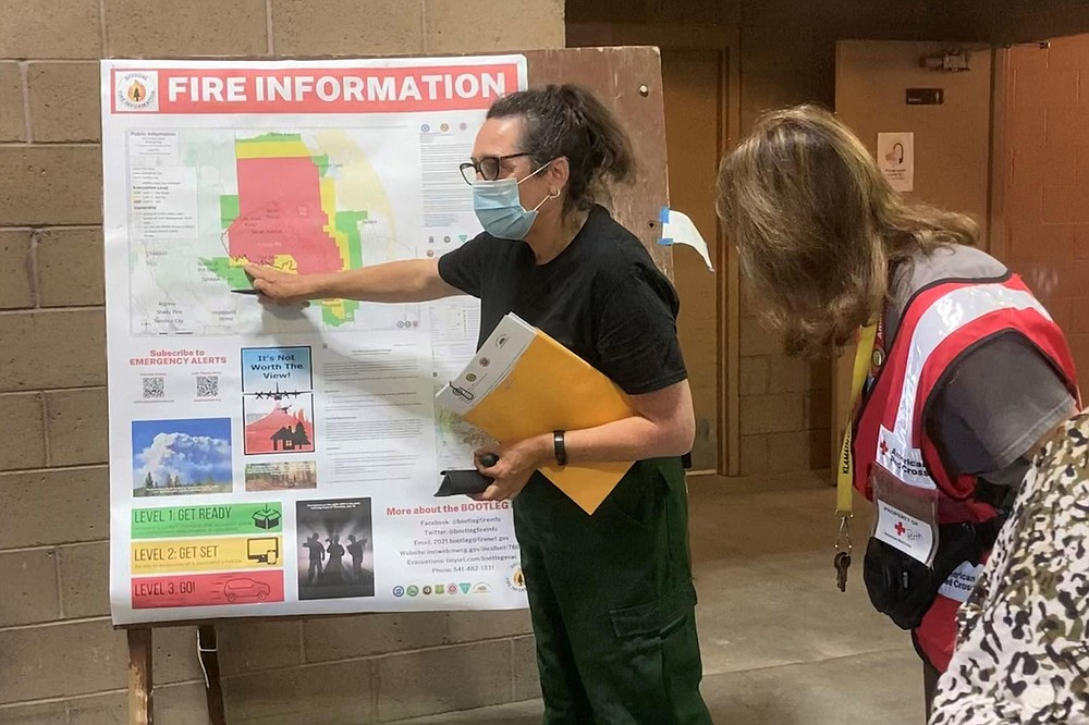 In this photo provided by the Bootleg Fire Incident Command, a public information officer talks with evacuees at a Red Cross Shelter near the Bootleg Fire in southern Oregon, Sunday, July 18, 2021. The destructive Bootleg Fire, one of the largest in modern Oregon history, has already burned more than 476 square miles (1,210 square kilometers), an area about the size of Los Angeles. Meteorologists predicted critically dangerous fire weather through at least Monday with lightning possible in both California and southern Oregon. (Bootleg Fire Incident Command via AP)