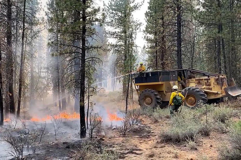 In this photo provided by the Bootleg Fire Incident Command, firefighters battle the Bootleg Fire in southern Oregon, Saturday, July 17, 2021. Meteorologists predicted critically dangerous fire weather through at least Monday with lightning possible in both California and southern Oregon. (J. Michael Johnson/Bootleg Fire Incident Command via AP)