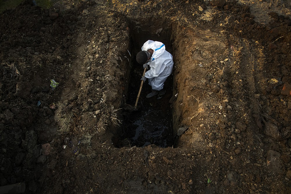 FILE - In this April 25, 2021, file photo, a man in protective suit digs earth to bury the body of a person who died of COVID-19 in Gauhati, India. India's excess deaths during the pandemic could be a staggering 10 times the official COVID-19 toll, likely making it modern India's worst human tragedy, according to the most comprehensive research yet on the ravages of the virus in the south Asian country. (AP Photo/Anupam Nath, File)
