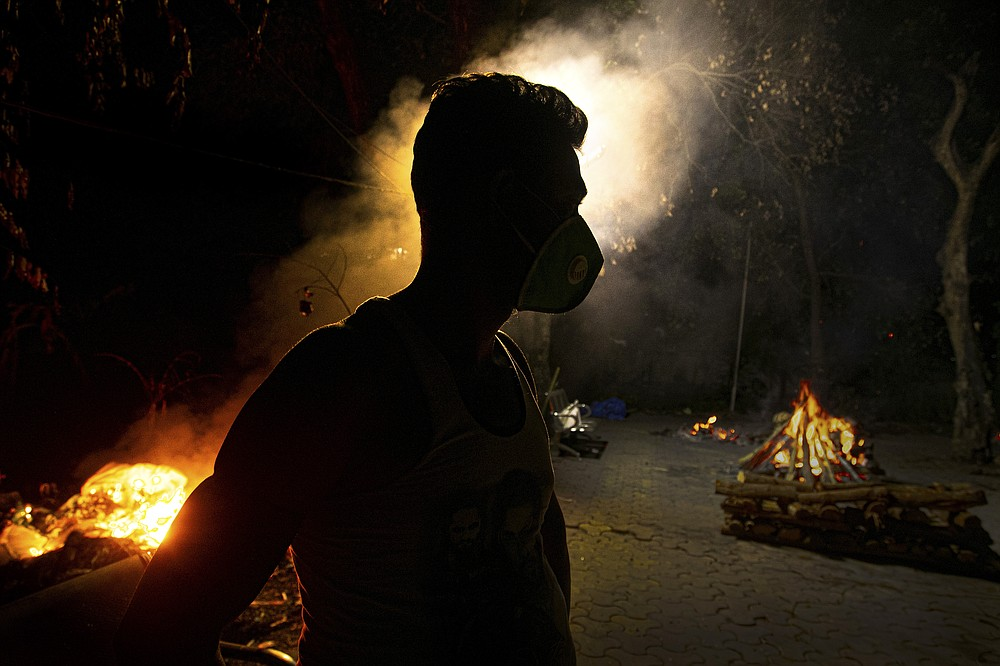 FILE - In this Sept. 14, 2020, file photo, Ramananda Sarkar, 43, who has cremated more than 450 COVID-19 victims stands by burning funeral pyres of COVID-19 victims in Gauhati, India. India's excess deaths during the pandemic could be a staggering 10 times the official COVID-19 toll, likely making it modern India's worst human tragedy, according to the most comprehensive research yet on the ravages of the virus in the south Asian country. (AP Photo/Anupam Nath, File)