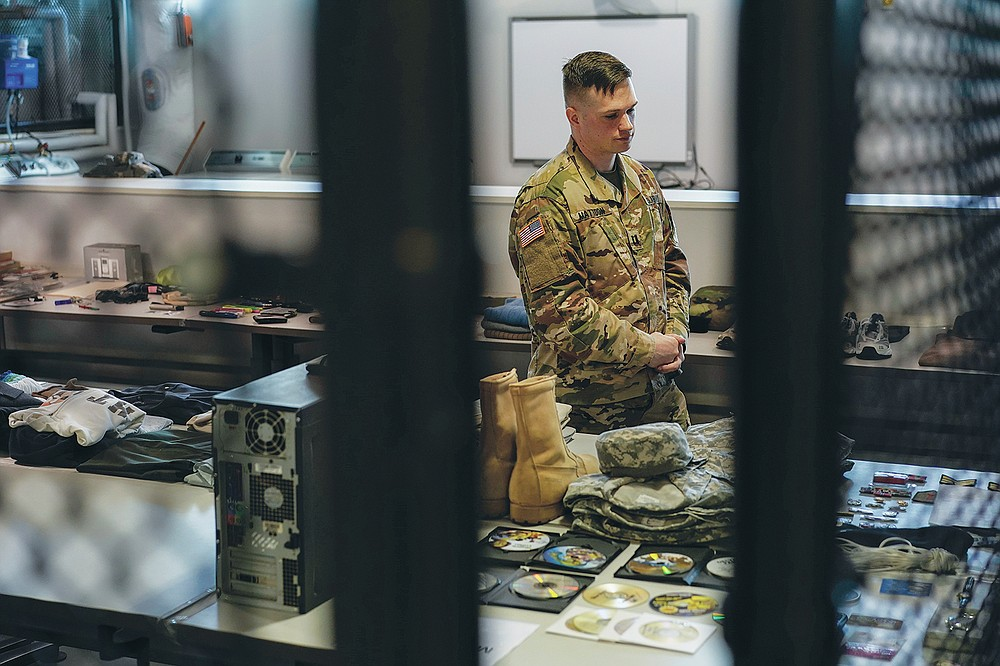 Army Capt. Geoffrey C. Mattoon stands among examples deceased service members belongings at the Joint Personal Effects Depot on Dover Air Force Base, Del., Monday, June 21, 2021. The depot is where the personal effects of deceased service members are processed as part of the dignified transfer. (AP Photo/Carolyn Kaster)