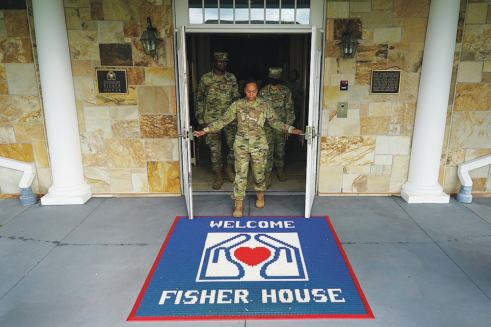 Tech Sgt. Ashley Harrell, joined by Senior Airman Myguerson Sainvilus, left, and Senior Airman lyana Green right, opens the doors of Dover Fisher House at Dover Air Force Base, Del., Monday, June 21, 2021. Dover Fisher House provides short-term, on-base lodging to families who travel to Dover Air Force base to witness the dignified transfer of their loved ones. (AP Photo/Carolyn Kaster)