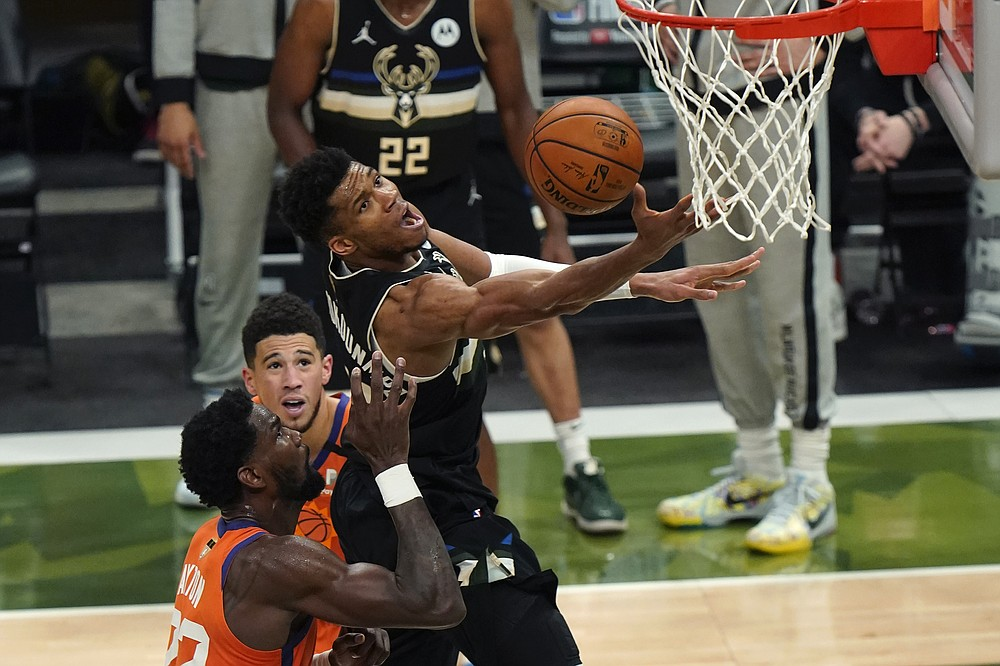 Milwaukee Bucks forward Giannis Antetokounmpo (34) goes to the basket over Phoenix Suns center Deandre Ayton (22) and guard Devin Booker during the second half of Game 6 of basketball's NBA Finals in Milwaukee, Tuesday, July 20, 2021. (AP Photo/Paul Sancya)