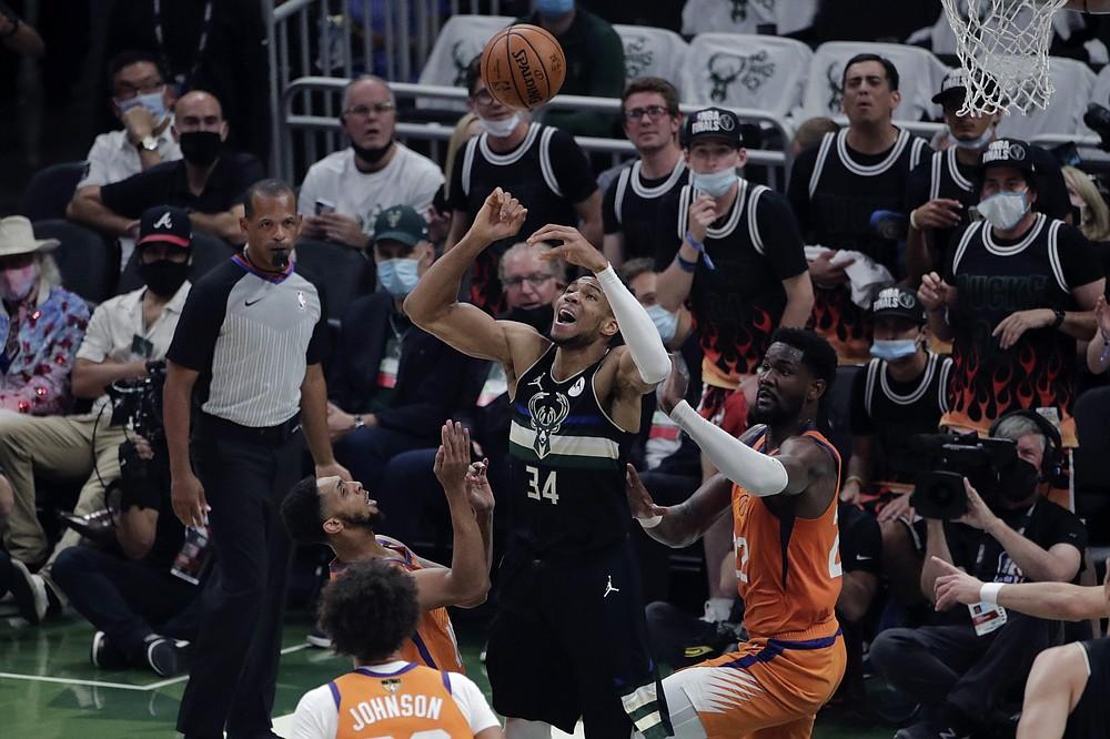 Milwaukee Bucks forward Giannis Antetokounmpo (34) battles between Phoenix Suns forward Cameron Johnson and Phoenix Suns center Deandre Ayton (22) during the first half of Game 6 of basketball's NBA Finals Tuesday, July 20, 2021, in Milwaukee. (AP Photo/Aaron Gash)