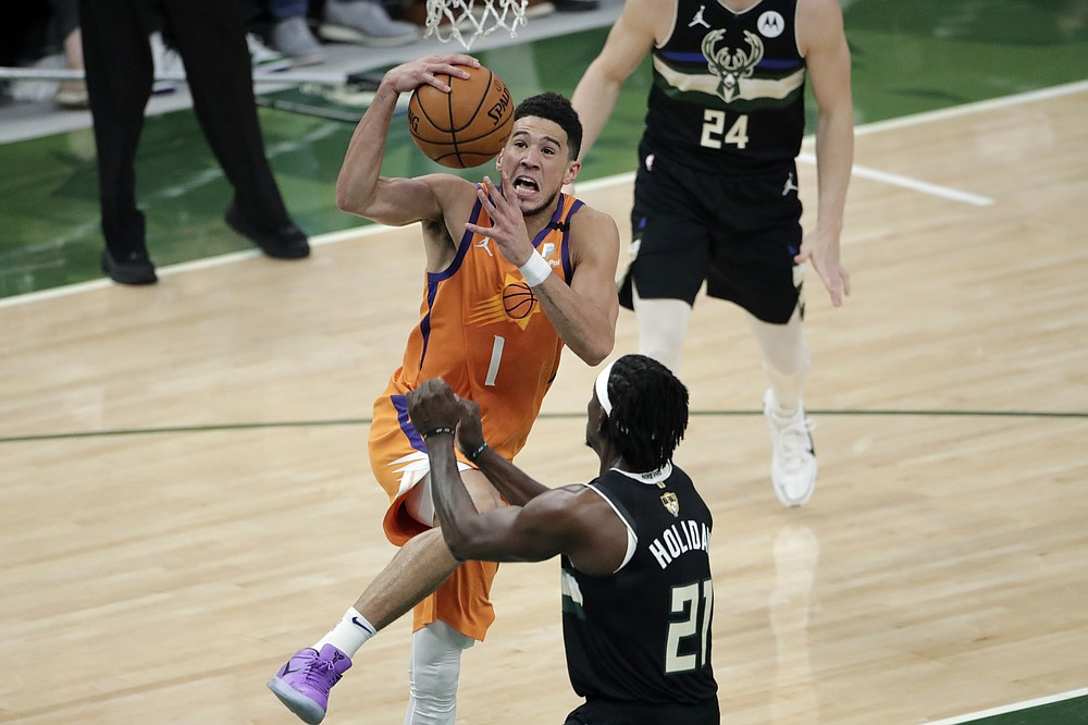 Phoenix Suns guard Devin Booker (1) drives to the basket against Milwaukee Bucks guard Jrue Holiday (21) during the first half of Game 6 of basketball's NBA Finals Tuesday, July 20, 2021, in Milwaukee. (AP Photo/Aaron Gash)
