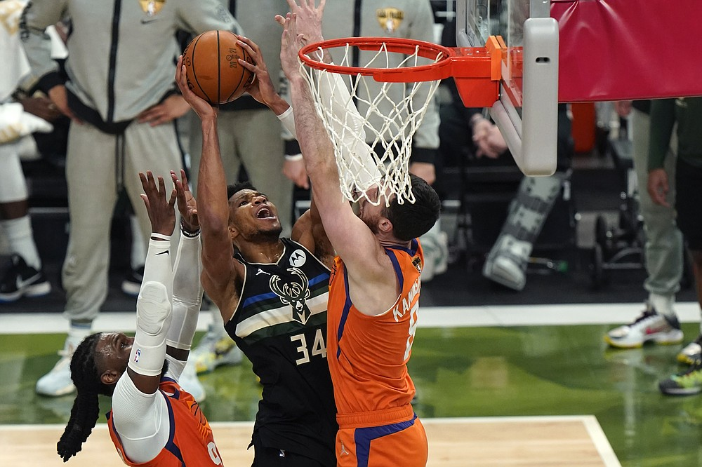 Milwaukee Bucks forward Giannis Antetokounmpo (34) goes to the basket between Phoenix Suns forward Frank Kaminsky, right, and forward Jae Crowder during the second half of Game 6 of basketball's NBA Finals in Milwaukee, Tuesday, July 20, 2021. (AP Photo/Paul Sancya)