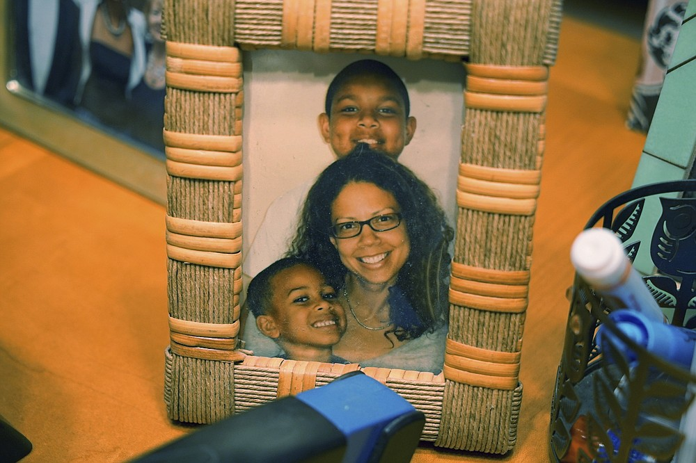 A photo of Alton Lucas' wife, Bronwyn Lucas, and their children, sits on a desk at his home outside of Raleigh, N.C., on Friday, June 18, 2021. His wife, whom he'd met at a fatherhood counseling conference, said his past had barred him from doing something as innocuous as chaperoning their children on school field trips. (AP Photo/Allen G. Breed)
