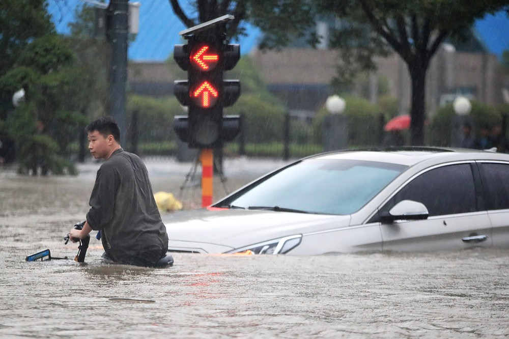 A man rides a bicycle through a flooded intersection in Zhengzhou in central China's Henan Province, Tuesday, July 20, 2021. China's military has blasted a dam to release floodwaters threatening one of its most heavily populated provinces. The operation late Tuesday night in the city of Luoyang came after several people died in severe flooding in the Henan provincial capital of Zhengzhou, where residents were trapped in the subway system and left stranded at schools, apartments and offices. (Chinatopix via AP)