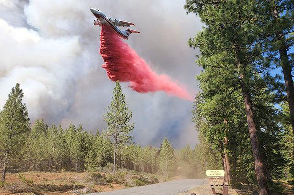 In this photo provided by the Bootleg Fire Incident Command, a tanker drops retardant over the Mitchell Monument area at the Bootleg Fire in southern Oregon on Saturday, July 17, 2021. The 569-square-mile (1,474 square kilometers) Bootleg Fire is burning 300 miles (483 kilometers) southeast of Portland in and around the Fremont-Winema National Forest, a vast expanse of old-growth forest, lakes and wildlife refuges. (Bootleg Fire Incident Command via AP)