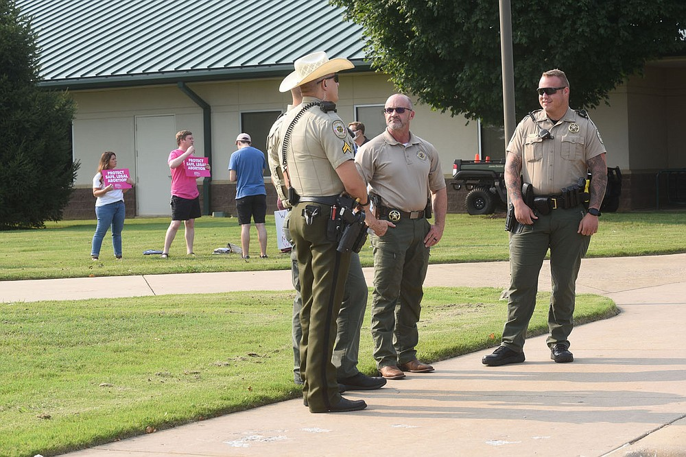 Benton County deputies and sign carriers stand Tuesday July 20 2021 at the meeting entrance at Northwest Arkansas Community College. (NWA Democrat-Gazette/Flip Putthoff)