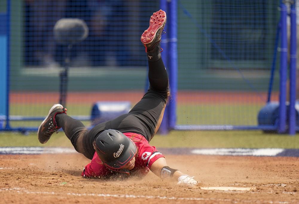 Canada's Joey Lye falls at home plate during the softball game between the United States and Canada at the 2020 Summer Olympics, Thursday, July 22, 2021, in Fukushima , Japan. (AP Photo/Jae C. Hong)