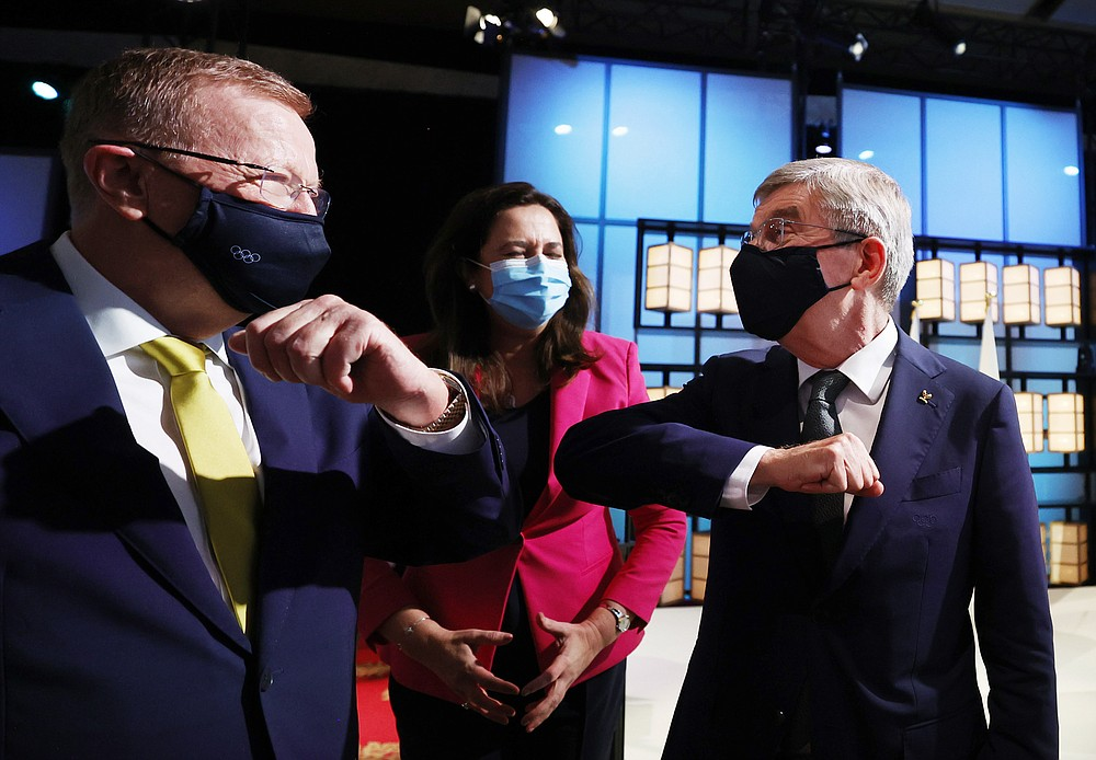 President of the International Olympic Committee Thomas Bach, right, bumps elbows with members of the Brisbane 2032 delegation, from left, John Coates AC, President, Australian Olympic Committee and The Honourable Annastacia Palaszczuk MP, Premier of Queensland and Minister for Trade, after Brisbane was announced as the 2032 Summer Olympics host city during the IOC Session at Hotel Okura in Tokyo, Wednesday, July 21, 2021. (Toru Hanai/Pool Photo via AP)