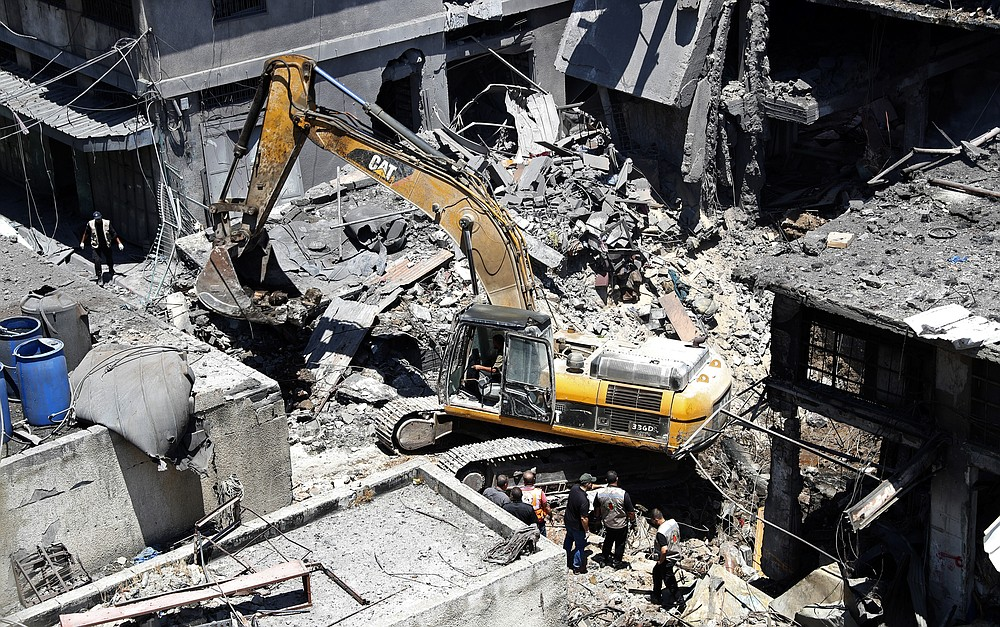 Palestinian rescuers and security personnel inspect the site of an explosion as a mechanical digger works to remove rubble, in Gaza City, Gaza, Thursday, July 22, 2021. At least one person was killed and 10 injured Thursday when an explosion tore through a house in a popular market, the interior ministry said. (AP Photo/Adel Hana)