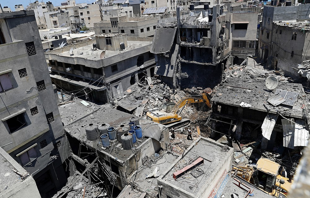 Palestinian security officers watch as a mechanical digger works to remove rubble at the site of an explosion in the Al-Zawiya market, in Gaza City, Gaza, Thursday, July 22, 2021. At least one person was killed and some 10 injured Thursday when the explosion tore through a house in a popular market, the interior ministry said. (AP Photo/Adel Hana)