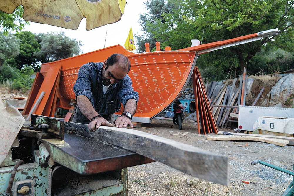 Giorgos Kiassos, one of the last remaining boatbuilders on Samos island, uses a hand plane to shape wood to be used for the frame of a traditional boat on Thursday, June 10, 2021, at his mountain boatyard in the village of Drakaioi. The art of designing and building these vessels, which is done entirely by hand, is under threat. Fewer wooden boats are being ordered, with plastic and fiberglass ones cheaper to maintain. (AP Photo/Petros Giannakouris)
