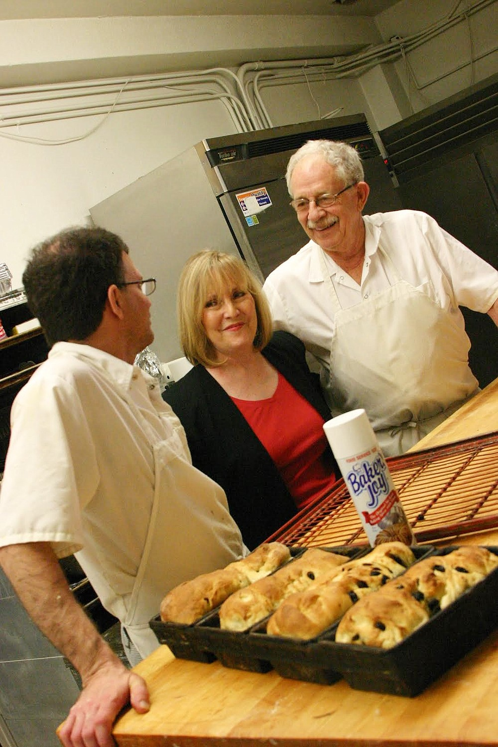 From left, youngest son Paul Klappenbach is in the kitchen with regular customer Marilyn Book and master baker Norman August Klappenbach. (Special to The Commercial/Deborah Horn)