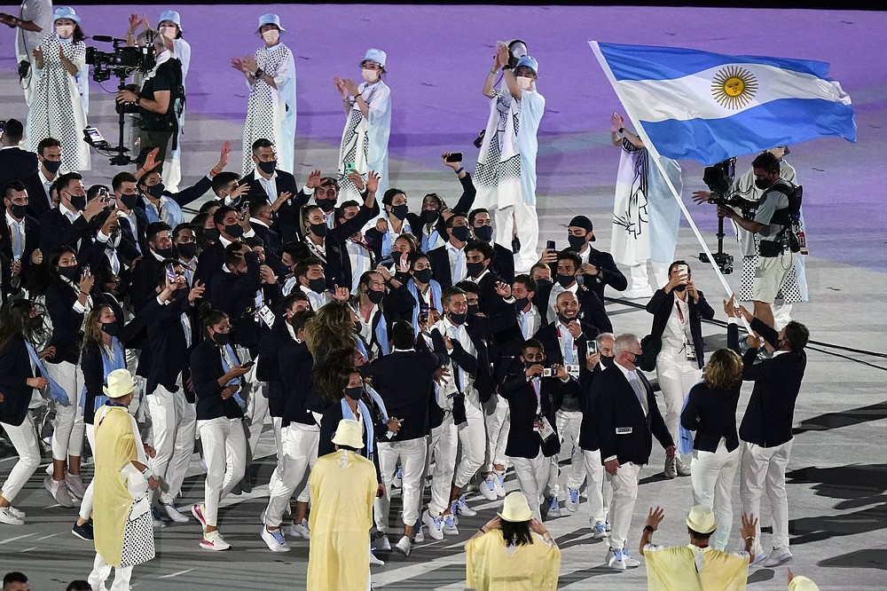Cecilia Carranza Saroli and Santiago Raul Lange, of Argentina, right, carry their country's flag during the opening ceremony in the Olympic Stadium at the 2020 Summer Olympics, Friday, July 23, 2021, in Tokyo, Japan. (AP Photo/Patrick Semansky)
