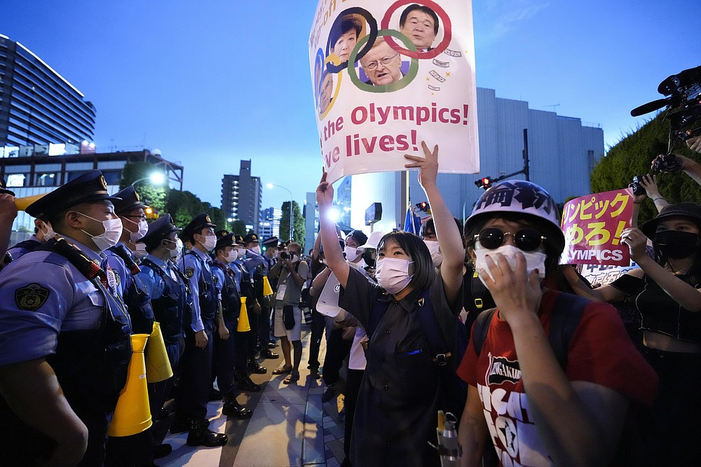 Anti-Olympics protesters, right, stage a rally in front of lines of policemen near National Stadium in Tokyo Friday, July 23, 2021.  (Ryosuke Uematsu/Kyodo News via AP)