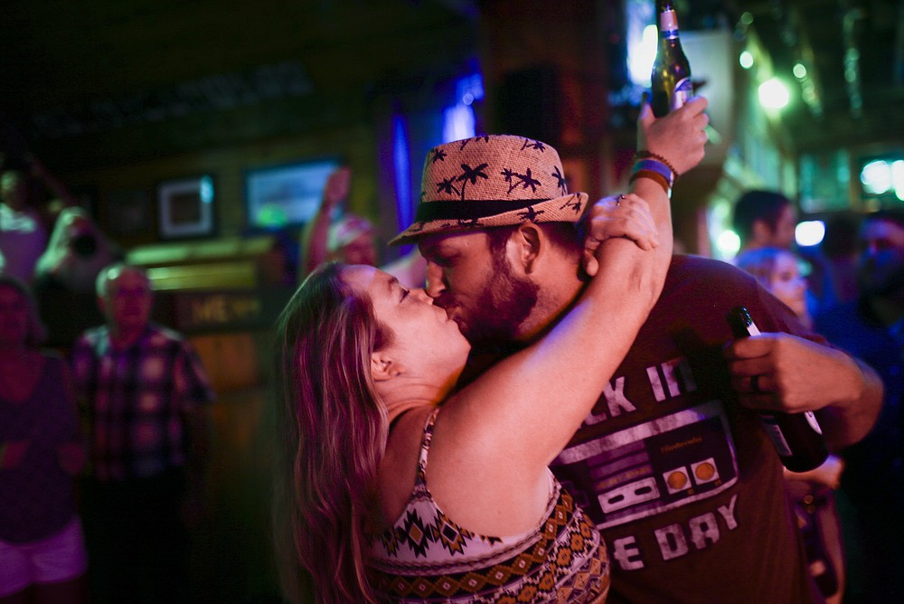 Amber Mills (from left) kisses Ira Mills, Saturday, July 17, 2021 at George's Majestic Lounge in Fayetteville. Check out nwaonline.com/210718Daily/ for today's photo gallery.  (NWA Democrat-Gazette/Charlie Kaijo)